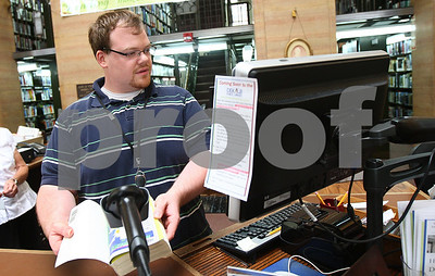 Kyle Bursaw – kbursaw@shawmedia.com  Circulation Clerk Patrick Harding checks a book back into the computer system at the DeKalb Public Library on Friday, June 29, 2012. The library will be transitioning to new circulation software over the holiday and publicly available computers will be down from July 1st through 5th.