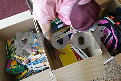 Rob Winner – rwinner@shawmedia.com  Matthew Clark of The House Cafe sorts a box of unused notebooks and binders during the fourth annual Music Show: Collecting School Supplies at The House Cafe in DeKalb Sunday afternoon. Guests to the event brought school supplies to benefit the Salvation Army in DeKalb.