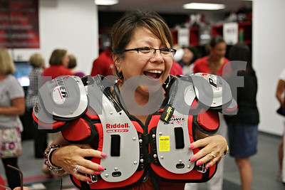 Rob Winner – rwinner@shawmedia.com  Gwen Haigler of Sycamore tries on shoulder pads inside the Northern Illinois football team's locker room during the Football 101 Women's Clinic Wednesday evening.