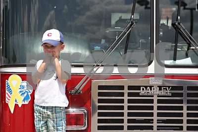 Rob Winner – rwinner@shawmedia.com  Tommy Padilla, 2 of Malta, stands on the bumper of a fire engine and smiles for his grandmother Anne Roussell (not pictured) before a dedication ceremony honoring Timothy Getzelman and Alexi Weber at the Sycamore Fire Department Fire Station No. 2 Sunday afternoon.