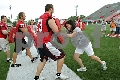 Rob Winner – rwinner@shawmedia.com  Pam Nelson of Sycamore participates in a blocking drill with Northern Illinois offensive lineman Matt Killian during the Northern Illinois Football 101 Women's Clinic Wednesday evening.
