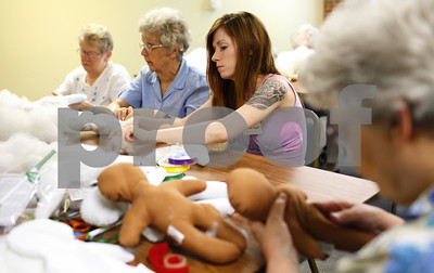 Kyle Bursaw – kbursaw@shawmedia.com  Volunteers Judy Lawrence (from left), Jane Bastian and Rebeka Appel stuff trauma dolls, as June Tritt (far right) checks the quality of the stuffed dolls before they are sewed shut at Oak Crest in DeKalb, Ill. on Wednesday, July 11, 2012.