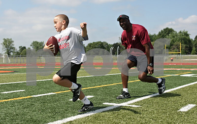 Rob Winner – rwinner@shawmedia.com  After hauling in a pass from Steve Fuller (not pictured), Justin Hatton, 8 of DeKalb, makes a move on Otis Wilson before reaching the end zone during a football camp featuring former members of the 1985 Chicago Bears at DeKalb High School Friday morning.