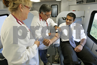 Rob Winner – rwinner@shawmedia.com  Phlebotomists Joan Falkenhan (from left to right) and Odie Hernandez work on locating a vein on Axay Doshi's arm during an American Red Cross blood drive outside the Castle Bank on Greenwood Avenue in DeKalb Thursday afternoon.