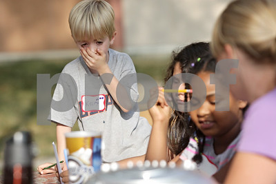 Rob Winner – rwinner@shawmedia.com  Kasey Jones, 6, and a group of children try to figure out the sound of an animal at the start of a free summer reading vacation program presented by Neighbors' House outside the Gideon Court Apartments in DeKalb Tuesday.