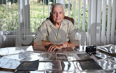 Kyle Bursaw – kbursaw@shawmedia.com  Frank Paciga, 86, spent three years during World War II as a combat photographer for the United States. Paciga is seen here in his Kingston home with one of his cameras and several photos from his collection spread out on the table.  Taken Thursday, July 5, 2012.