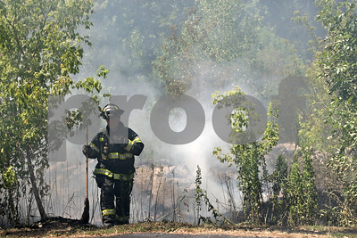 Rob Winner – rwinner@shawmedia.com  A DeKalb Firefighter leaves a wooded area near Breezy's Discount Storage in DeKalb after controlling a fire Wednesday afternoon.