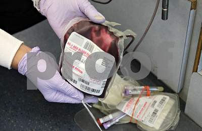 Rob Winner – rwinner@shawmedia.com  Phlebotomist Joan Falkenhan shakes a blood donation bag to prevent clotting during an American Red Cross blood drive outside the Castle Bank on Greenwood Avenue in DeKalb Thursday afternoon.