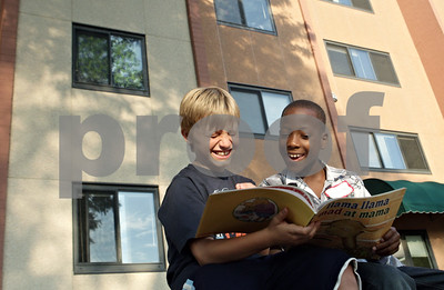 Rob Winner – rwinner@shawmedia.com  William Moon (left), 9, and Kenneth Weeks, 8, take turns reading a book outside Gideon Court Apartments in DeKalb Tuesday evening. The two were participating in a free summer reading vacation program presented by Neighbors' House.