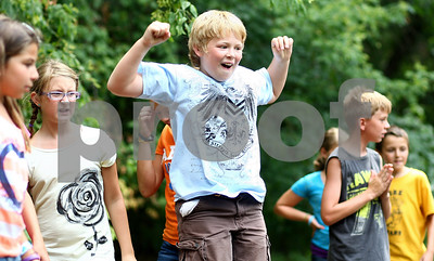 Kyle Bursaw – kbursaw@shawmedia.com  Andrew Russo, 11, a participant in the 'Out of School Care and Recreation' program celebrates as it appears his team's boat made out of recycled and natural materials will win a race in the river at Sycamore Park on Friday, July 13, 2012.