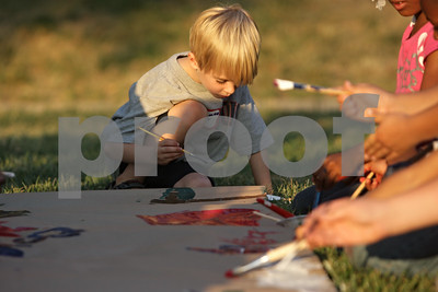 Rob Winner – rwinner@shawmedia.com  Kasey Jones, 6, helps paint a mural with a group of children outside Gideon Court Apartments in DeKalb Tuesday night. The group of children were participating in a free summer reading vacation program presented by Neighbors' House.