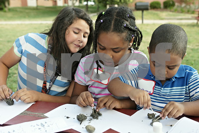 Rob Winner – rwinner@shawmedia.com  (From left to right) Marcella Solis, 10, Reem Eltayeb, 8, and Mohamad Eltayeb, 3, examine owl pellets outside the Gideon Court Apartments in DeKalb Tuesday evening as part of a free summer reading vacation program presented by Neighbors' House.