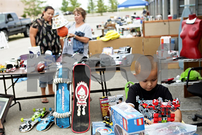 Rob Winner – rwinner@shawmedia.com  Silas Henderson, 4 of Sycamore, checks out some Lego toys at Home Town Storage during the community-wide garage sales event in Genoa Friday afternoon.