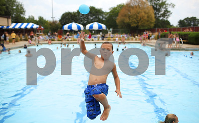 Kyle Bursaw – kbursaw@shawmedia.com  Nick Brown, 8, a participant in the 'Out of School Care and Recreation' program launches a ball as he leaps backwards in to the pool at Sycamore Park on Friday, July 13, 2012.