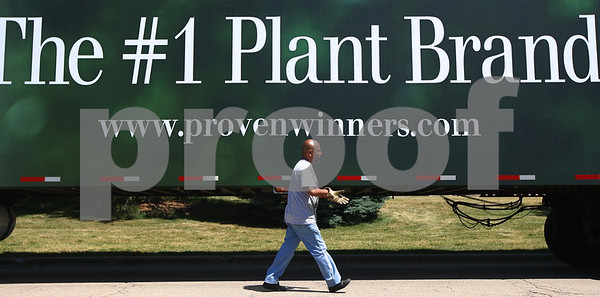 Kyle Bursaw – kbursaw@shawmedia.com  Baldo Reyes of Proven Winners walks to the back of the truck to unload another of the 40 planters being placed throughout DeKalb and the Northern Illinois University campus on Tuesday, June 12, 2012.