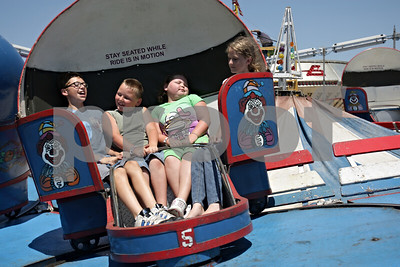 Rob Winner – rwinner@shawmedia.com  (From left to right) Siblings Daniel Hayward, 11, D.J. Hayward, 7, D'laney Hayward, 7, and their cousin Kayla Carpenter, 12, take a spin on the Tilt-A-Whirl ride during the annual Malta Days Festival Saturday.