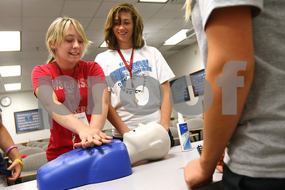 Kyle Bursaw – kbursaw@shawmedia.com  Morgan McCannon (left), from Paw Paw, and Kayleigh Kozlowski, from DeKalb practice doing CPR compressions on a dummy with camp counselor Katie Paige (right), a University of Illinois-Champaign graduate student, looks on during the Rural Health Careers Camp held at NIU on Wednesday, June 13, 2012.
