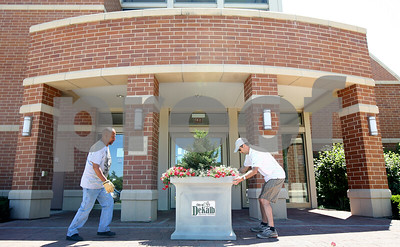 Kyle Bursaw – kbursaw@shawmedia.com  Baldo Reyes (left) and Marshall Dirks of Proven Winners position a planter in front of the Barsema Alumni and Visitors Center on Tuesday, June 12, 2012. The planter was one of 40 to be placed on campus and around DeKalb.