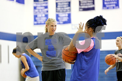 Rob Winner – rwinner@shawmedia.com  Rosary High School's new varsity basketball coach Jessie Wilcox (left) talks with Siobhan Midgley before practice Tuesday in Aurora. Wilcox is played for the Northern Illinois basketball team from 2004 to 2009.