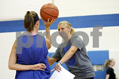 Rob Winner – rwinner@shawmedia.com  Former Northern Illinois basketball player Jessie Wilcox (right) works with Kayla Emory during practice Tuesday in Aurora. Wilcox is the new varsity basketball coach at Rosary High School.