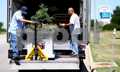 Kyle Bursaw – kbursaw@shawmedia.com  Esteban Rarmos (left) and Baldo Reyes of Proven Winners unload one of the planters from their truck to place in front of the Human Resources and Document Services building at Northern Illinois University on Tuesday, June 12, 2012.