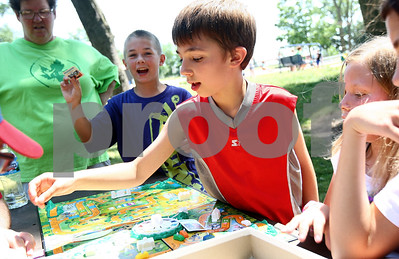 Kyle Bursaw – kbursaw@shawmedia.com  While playing The Game of Life at Hopkins Park, Anthony Grych (center), 9, draws cards for his occupation and salary and Bradford Edwards (left) celebrates getting police officer as an occupation on Monday, June 18, 2012.