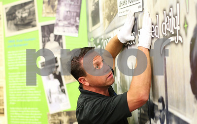 Kyle Bursaw – kbursaw@shawmedia.com  Jeff Rhoades presses a panel of Lehan Drugs' new history wall into the special tape behind it to secure it in place on Wednesday, June 13, 2012. Rhoades works for Kelmscott communications and the wall was designed by OC Imageworks.