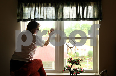 Kyle Bursaw – kbursaw@shawmedia.com  Ann Elliot, of Castle Bank, chats with Heritage Woods resident Nancee Jones while washing Jones' window in DeKalb, Ill. on Thursday, June 21, 2012 as part of the Kishwaukee United Way's annual Day of Caring.