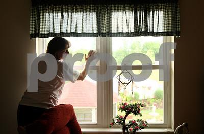 Kyle Bursaw – kbursaw@shawmedia.com  Ann Elliot, of Castle Bank, chats with Heritage Woods resident Nancee Jones while washing Jones' window in DeKalb, Ill. on Thursday, June 21, 2012 as part of the Kishwaukee United Way's annual Day of Caring.