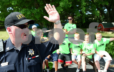 Kyle Bursaw – kbursaw@shawmedia.com  Sgt. Brad Carls of the DeKalb County Sheriff's Department demonstrates bicycle turn signals for a group of children at the DeKalb County Farm Bureau's Farm Safety Camp at Jonamac Orchard in Malta, Ill. on Wednesday, June 20, 2012.