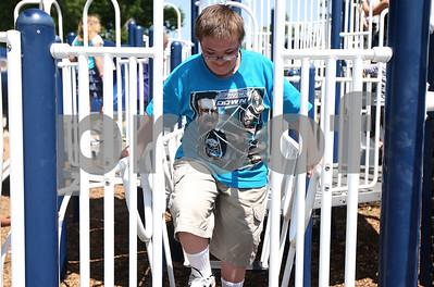 Kyle Bursaw – kbursaw@shawmedia.com  J.T. Baine, 13, roams the Hopkins Park playground under the supervision of the Camp Maple Leaf counselors on Monday, June 18, 2012.