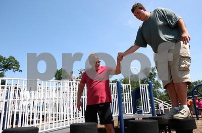 Kyle Bursaw – kbursaw@shawmedia.com  Mike Franckowiak, a group leader and  counselor with Camp Maple Leaf, gives Larry Cox a helping hand as he navigates an obstacle on the Hopkins Park playground on Monday, June 18, 2012.