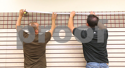 Kyle Bursaw – kbursaw@shawmedia.com  Noe Rosas (left) and Jeff Rhoades put up a high-bonding type of tape on the wall at Lehan Drugs' to eventually put up the company's new history wall on Wednesday, June 13, 2012. Rhoades works for Kelmscott communications and Rosas was assisting him on the project.