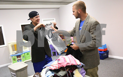 Kyle Bursaw – kbursaw@shawmedia.com  Jared Tomany and Joey Burney, both players for the DeKalb County Liners, check out some of the designs while helping sort donated clothes by size, type and gender at Feed'em Soup in DeKalb, Ill. on Thursday, June 21, 2012 as part of Kishwaukee United Way's annual Day of Caring.