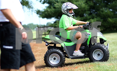 Kyle Bursaw – kbursaw@shawmedia.com  Karyn Baldwin, 12, rides a small ATV under the supervision of Bob Schenck (left) of OpenAir Powersports, who was there teaching ATV safety at the DeKalb County Farm Bureau's Farm Safety Camp at Jonamac Orchard in Malta, Ill. on Wednesday, June 20, 2012.