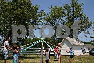 Children and adults wind streamers around the maypole Sunday outside the old North Grove School on Brickville Road in Sycamore. An open house was held this past weekend to allow visitors to tour the one-room schoolhouse and celebrate the building being listed on the National Register of Historic Places.  Caitlin Mullen - cmullen@shawmedia.com