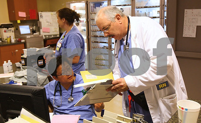 Kyle Bursaw – kbursaw@shawmedia.com  Dr. Young Kim (left) discusses care of a patient with nurse John Cox (right) in the emergency department of Kishwaukee Community Hospital on Thursday, June 28, 2012.