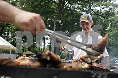 Rob Winner – rwinner@shawmedia.com  Angelo Tsiagalis (right), of DeKalb, helps turn grilled chicken seasoned with Greek spices during the annual Greek Fest at Hopkins Park Saturday afternoon. The festival, presented by St. George Greek Orthodox Church, was held Saturday and Sunday. The event featured authentic Greek food, music, dance performances and activities for children.