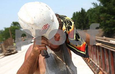 Kyle Bursaw – kbursaw@shawmedia.com  Jon Sprimont of D Construction, removes his hard hat for a moment to wipe off some sweat while working on the bridge on Bethany Road east of First Street on Thursday, June 28, 2012.