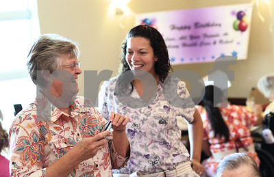 Kyle Bursaw – kbursaw@shawmedia.com  Lucille Larson's daughter Barb Voga (left) and Vanessa Hall, an R.C.N.A. at  Bethany Health Care and Rehab Center, try to get a Lucille Larson to smile for a picture on her 100th birthday on Tuesday, June 26, 2012.