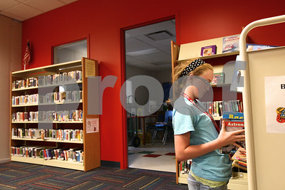 Kyle Bursaw – kbursaw@shawmedia.com  Volunteer Libby Swedberg, 12, puts away books that have been returned in their places in the children's section of Sycamore Public Library on Wednesday, June 27, 2012. The library recently entered the second of four phases of construction, opening up the newly renovated children's section last Friday.