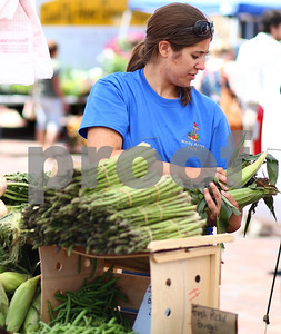 Kyle Bursaw – kbursaw@shawmedia.com  Leighanne Lacy restocks the Windy Acres Farm's produce table at the DeKalb farmer's market on Thursday, June 7, 2012.