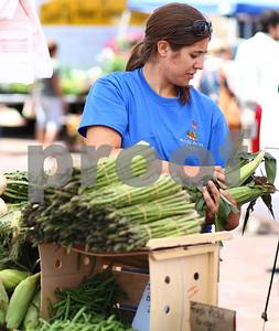 Kyle Bursaw – kbursaw@shawmedia.com  Leighanne Lacy restocks the Windy Acres Farm's produce table at the DeKalb farmer's market on Thursday, June 7, 2012.