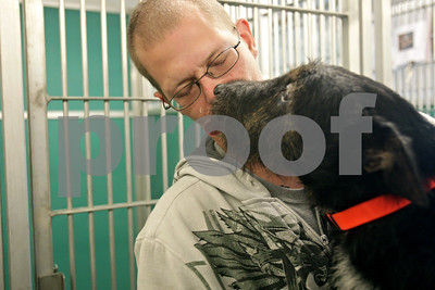 Rob Winner – rwinner@shawmedia.com  Jonathan Johnson is kissed by his 3-year-old-dog Chewy while visiting the DeKalb County Animal Shelter in Genoa Friday where three dogs and two cats of Johnson are temporarily living. The family was displaced after a fire in downtown Sycamore on May 24.