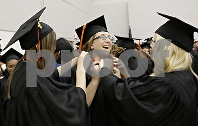 Rob Winner – rwinner@shawmedia.com  Savanna Meyers (center) is helped by classmates Cassie Lambert (left) and Jillian Smith (right) while putting on an alumni medal before the DeKalb High School graduation ceremony at the Convocation Center in DeKalb Thursday evening.