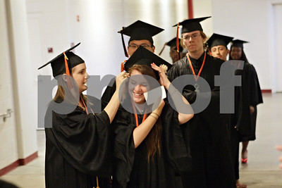 Rob Winner – rwinner@shawmedia.com  Sara Wuchte (left) helps classmate Alissa Witt moments before entering the floor of the Convocation Center for their graduation ceremony Thursday night.