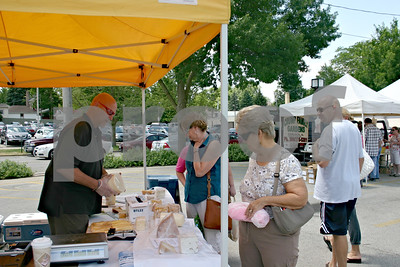 Rick Jones, head cheesemonger for The Cheese People of Beloit, Wis., wraps cheese as people browse the selection at the Sycamore farmers market Sunday at the corner of Somonauk and Elm streets in Sycamore.  Caitlin Mullen - cmullen@shawmedia.com