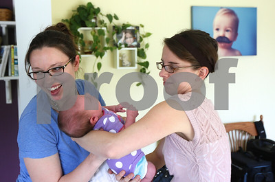 Kyle Bursaw – kbursaw@shawmedia.com  Doula Kim Wheaton hands two-week-old Abby back to her mom Chrissy Deming (left) at Deming's DeKalb home on Friday, May 25, 2012.