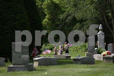 Rob Winner – rwinner@shawmedia.com  (From left to right) Matthew Searls, 12, his father Steve Searls and Ben Allen, 12, of Boy Scout Troop 4, look for the graves of veterans to place a U.S. flag Saturday morning at  Fairview Park Cemetery in DeKalb. Multiple scouts helped in the effort as part of an annual tradition before Memorial Day services.  DeKalb, Ill. Saturday, May 26, 2012