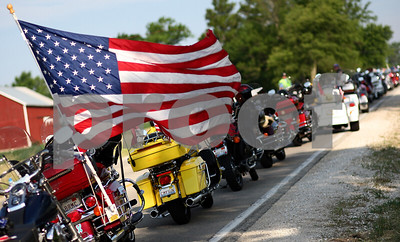 Kyle Bursaw – kbursaw@shawmedia.com  A flag attached to a motorcycle waves near the back of a line of motorcycles parked on Old State Road near Joiner Cemetery for the ceremony held there on the morning of Monday, May 28, 2012.